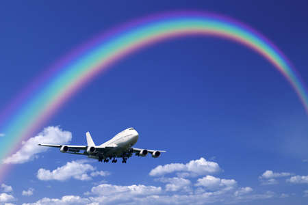 arc: A jetliner aeroplane flying over white clouds towards a rainbow in blue sky Stock Photo