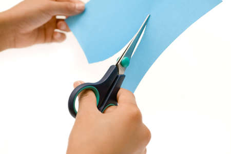 Hands holding a pair of scissora and cutting a piece of blue paper over white photo