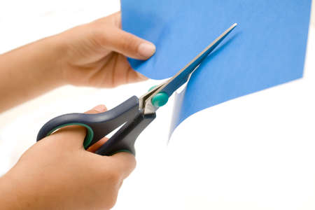 Hands holding a pair of household scissors cutting a sheet of blue paper over white photo
