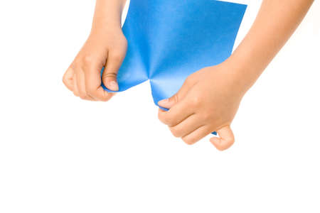 tearing: Hands tearing a sheet of blue paper over a white background