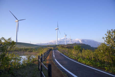 Wind turbines with a scenic snow-capped mountain photo