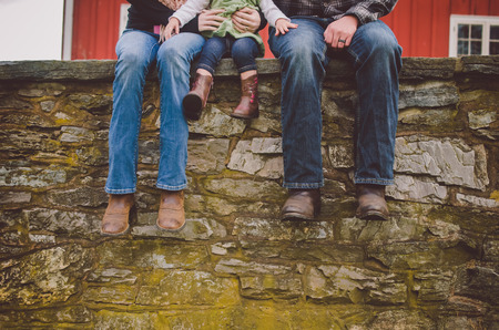 barn boots: A couple with a child sitting on a stone wall.