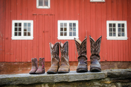 barn boots: A variety of sizes of cowboy boots in front of a red barn.