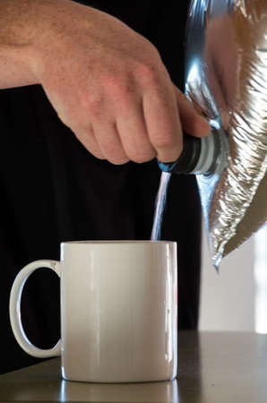 Goon sack pouring into a mug with a males hand in frame Stock Photo