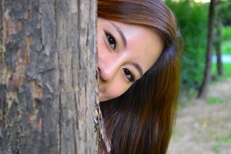 peek a boo: Hiding behind the tree  Stock Photo
