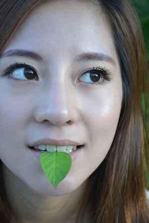 Beautiful young asian women with a leaf in mouth