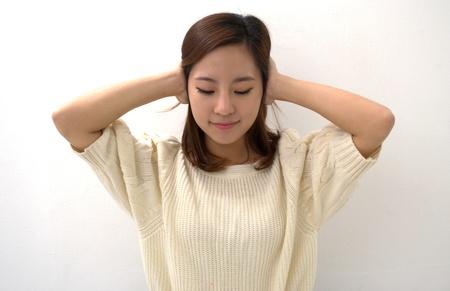 Girl keeps her ears shut isolated on white background