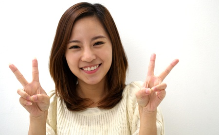 2 persons only: Smiling Young Woman Two Finger Peace Sign Hand Gesture Stock Photo