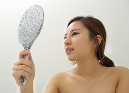 mirar espejo: Mujer inspeccionando su piel con un espejo