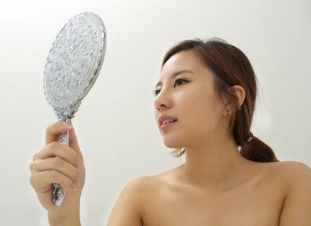 aging woman: Woman inspecting her skin with a mirror