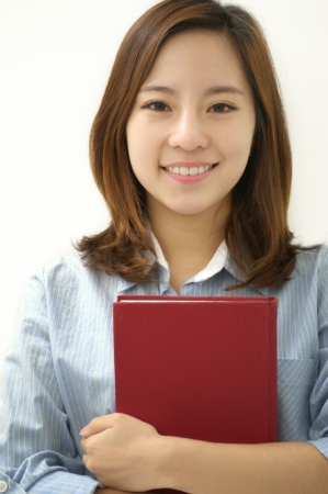 businesswoman smiling with a book on her chest