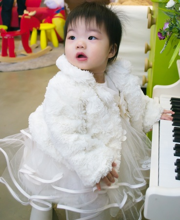 A baby playing on a toy piano photo