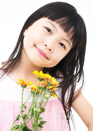Happy little asian girl with yellow daisy photo