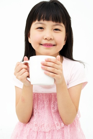 Beautiful little asian girl with mug isolated on white background
