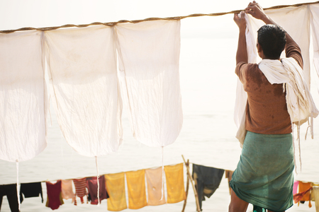 Indian old man hang the wash on a clothesline photo
