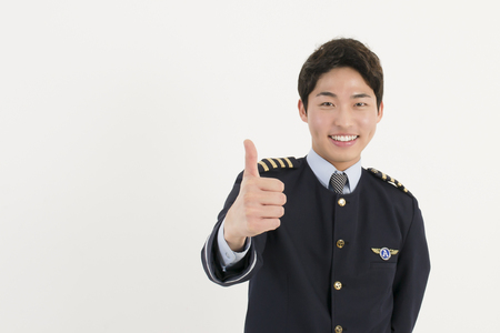 flight attendant: Cheerful airline pilot wearing uniform with thumb up gesture of approval Stock Photo