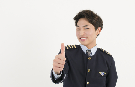Cheerful airline pilot wearing uniform with thumb up gesture of approval photo