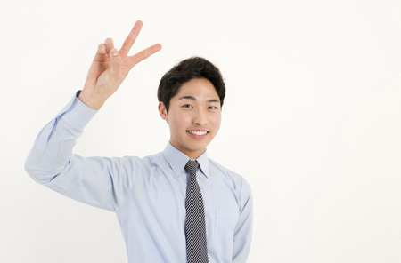 Smiling young businessman with two finger peace sign hand gesture photo