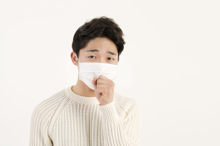 Asian man wearing a face mask with coughing Stock Photo