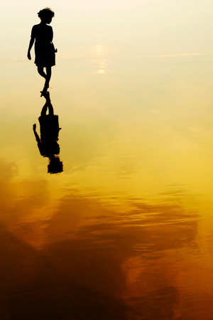 amarillo y negro: Una chica caminando en la playa al atardecer, la India Foto de archivo