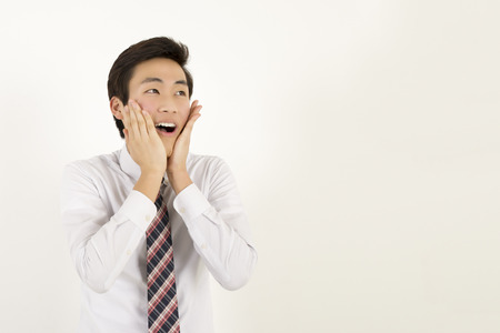 face work: Happy and amazed asian young man touching his face, shocked with unexpected promotion at work