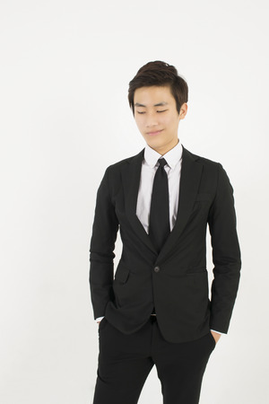 standing businessman: Asian young man in a black suit Stock Photo