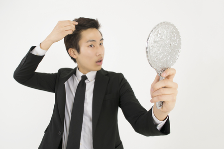 job loss: Asian young businessman in a black suit, looking at himself in a hand mirror