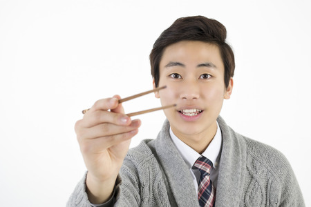 male hand: Asian young man try to catch something with chopsticks