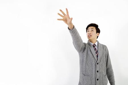 coger: El hombre asiático joven que intenta coger algo