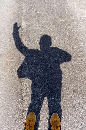 shadow man: Shadow of a man raising the left hand Stock Photo