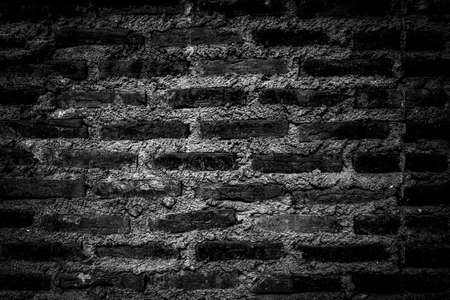 bw: Rustic bricks and cement texture wall in darkened b&w theme and high vignette for background use Stock Photo