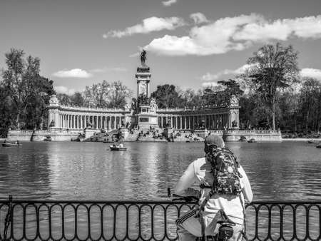 parque del buen retiro: A biker stops to take his breath at the pond in front of the Monument to Alfonso XII in Retiro Park, Madrid, Spain