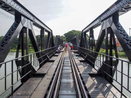 world war ii: KANCHANABURI, THAILAND - October 30, 2015: Unidentified people cross and take photos of the famous bridge over the river kwai in Kanchanaburi, Thailand. The bridge is an important landmark from the World War II Stock Photo