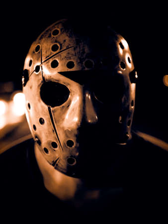 Low key image of a man wearing scary hockey mask for halloween