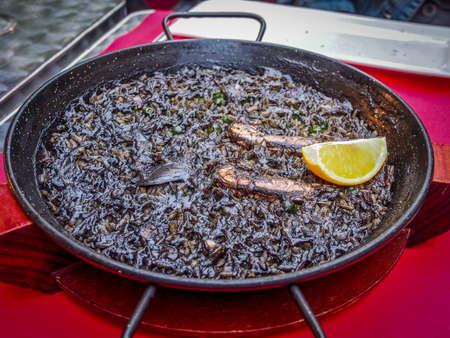 lemon wedge: Spanish Food: Black squid ink paella (Paella arroz negro) with lemon wedge