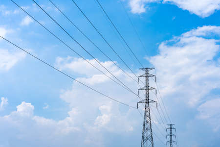 partly: High voltage power lines with partly cloudy blue sky in the background