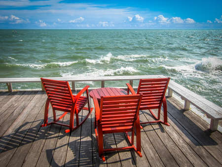 beach front: Rocking chairs on the wooden deck at beach front Stock Photo