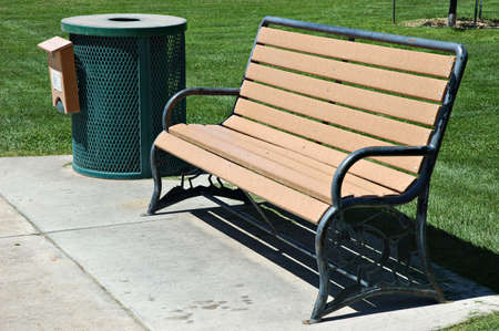 Park Bench and Trash Can with Grass and Sidewalk