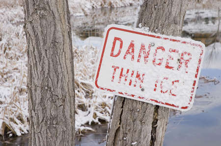 Danger Thin Ice Sign with Snow on It Nailed to a Tree