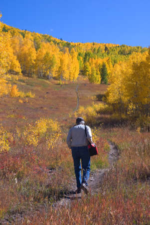 Man (my husband) hiking in autumn meadow on the Grand Mesa Stock Photo