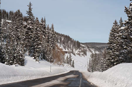 Horizontal shot of 2-lane scenic Highway 165 over the Grand Mesa in winter with recently plowed snow