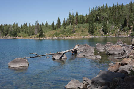 Big rocks from a slide have fallen far out into the clear waters of one of the Mesa Lakes on western Colorados Grand Mesa in this color photograph.