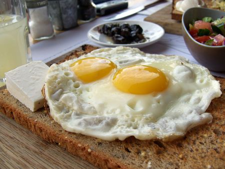 Close up of fresh breakfast with bread, fried eggs, salad and olive.