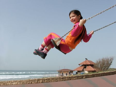 Smiling girl on swing against sky, sea beach in the background.