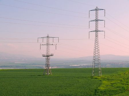 Two high voltage poles on background of morning sky and green field Stock Photo