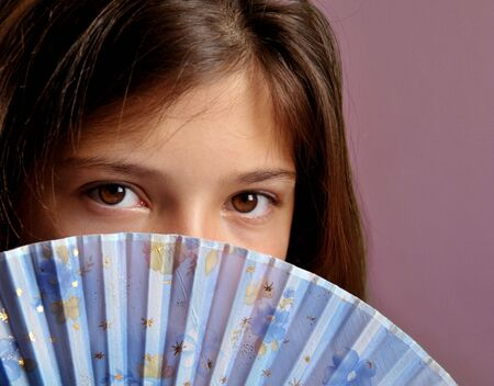 Portrait of young girl with fan.