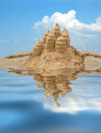 Sand castle on blue sky background with reflection on water Фото со стока