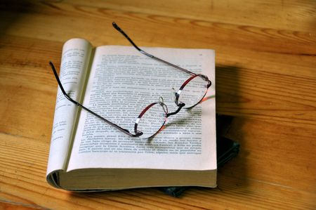 Close-up of opened book with glasses on wood background photo