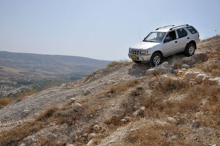 rough road: 4x4 vehicle driving down hill in a stone desert