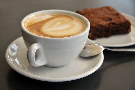 cappuccino: Close-up of coffee cup and brownies on a table Stock Photo